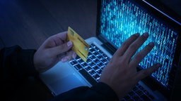 Hands of anonymous hackers holding credit card - stock photo