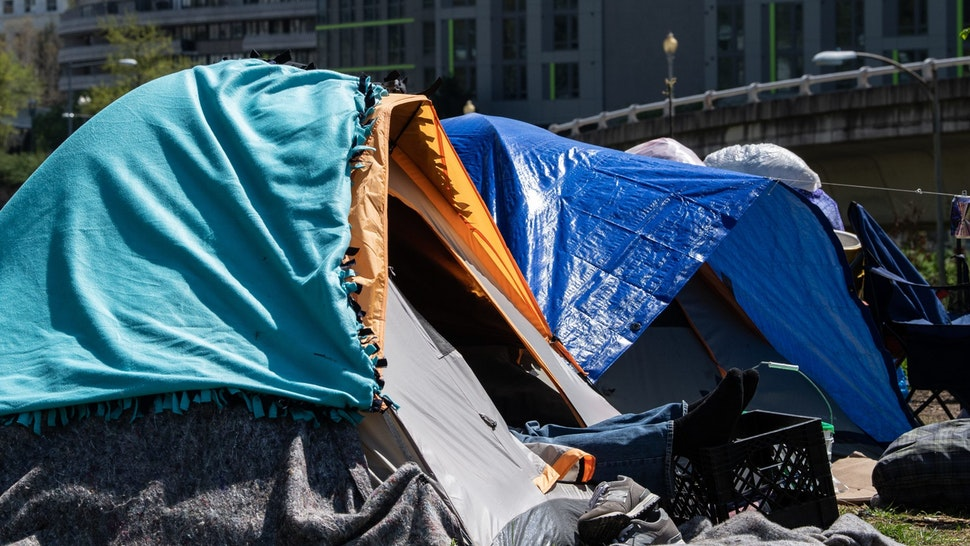 A homeless man rests in a tent in an encampment of homeless people in Washington, DC, on April 8, 2020. - The COVID-19 death toll in the US leapt to more than 15,000 Thursday, according to a running tally by Johns Hopkins University, from well over 400,000 confirmed cases.Meanwhile unemployment is rising at a jarring rate, with data Thursday showing 17 million have lost their jobs since mid-March, when America began shutting down. (Photo by NICHOLAS KAMM / AFP) (Photo by NICHOLAS KAMM/AFP via Getty Images)
