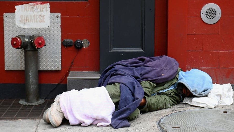 A homeless person sleeps near Madison Square Garden on April 29, 2020 in New York City - New York Citys homeless have sought refuge in the subways to escape the coronavirus pandemic, causing subway workers to ask the city for a solution.