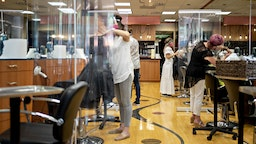 Stylists work behind plastic dividers at a hair salon in Arlington, Virginia, U.S., on Friday, May 29, 2020.