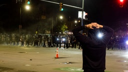 Police officers hold a line during a night of clashes between protesters and Detroit Police Officers, violence returned to downtown Detroit as police made dozens of arrests and fired tear gas and rubber bullets at protesters on May 30, 2020 in Detroit, Michigan.