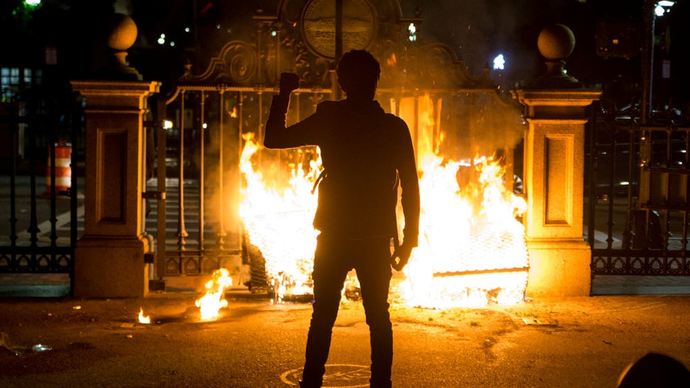 A protester holds up a fist in front of the burning gate of the Boston Public Garden as protestors try to barricade the police out as they get pushed through the Boston Commons on May 31, 2020.