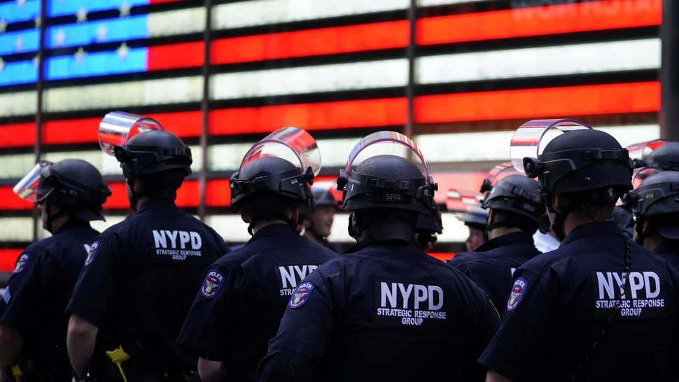 "TOPSHOT - NYPD police officers watch demonstrators in Times Square on June 1, 2020, during a ""Black Lives Matter"" protest. - New York's mayor Bill de Blasio today declared a city curfew from 11:00 pm to 5:00 am, as sometimes violent anti-racism protests roil communities nationwide. Saying that ""we support peaceful protest,"" De Blasio tweeted he had made the decision in consultation with the state's governor Andrew Cuomo, following the lead of many large US cities that instituted curfews in a bid to clamp down on violence and looting. (Photo by TIMOTHY A. CLARY / AFP) (Photo by TIMOTHY A. CLARY/AFP via Getty Images)"