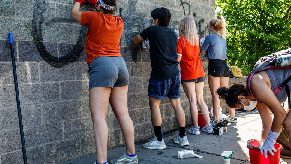 A group of volunteers cleans up a wall of a building vandalized and tagged with graffiti after a night of protests following the death in Minneapolis police custody of George Floyd on June 3, 2020 in Minneapolis, Minnesota.