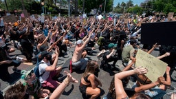 Demonstrators take a knee and put their hands up in front of officers from the Sheriff's Department as they protest the death of George Floyd, in West Hollywood, California on June 3, 2020.