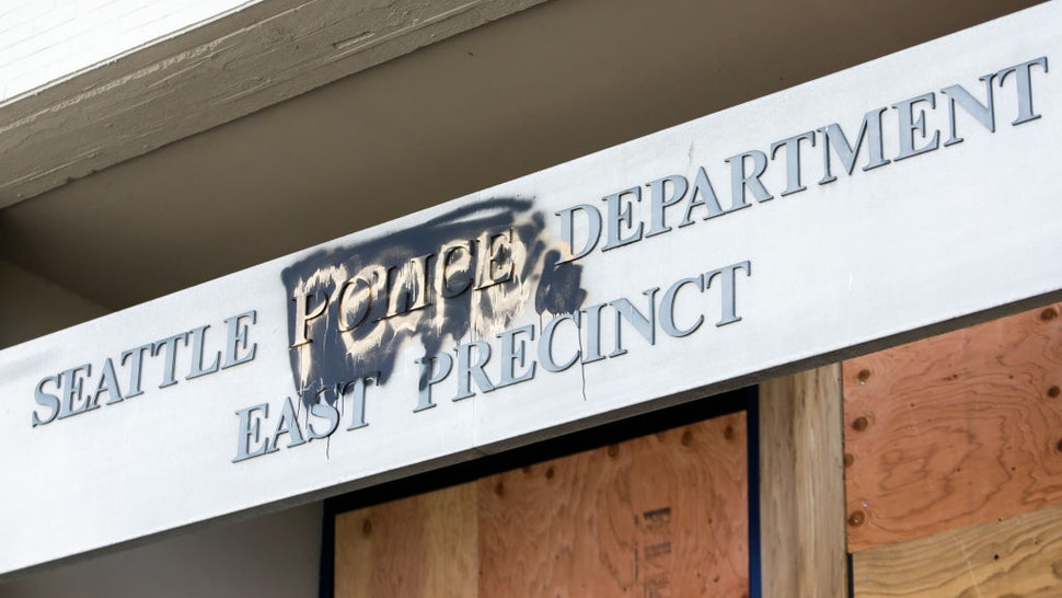 """The word """"people"""" is spray painted over the word """"police"""" on the closed Seattle Police Department's East Precinct now surrounded by the area known as the Capitol Hill Autonomous Zone (CHAZ), in Seattle, Washington on June 11, 2020."""