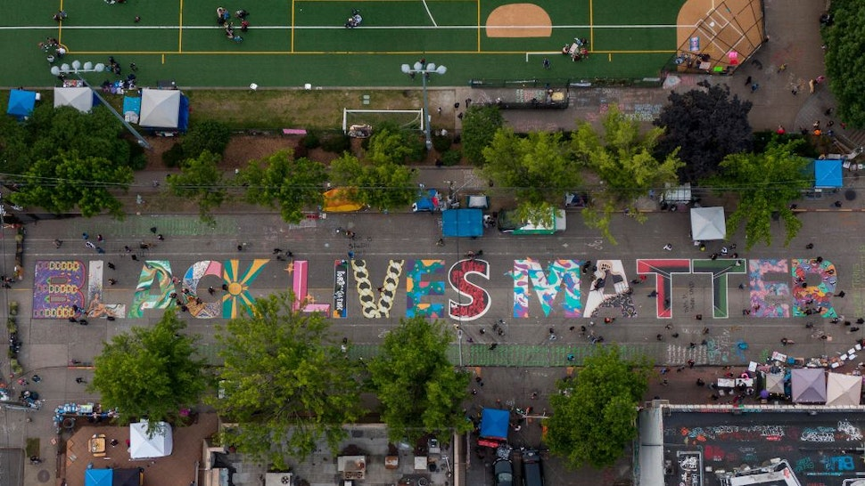 """An aerial view of a Black Lives Matter mural on East Pine Street near Cal Anderson Park is seen during ongoing Black Lives Matter events in the so-called """"CHOP,"""" an area that protesters have called both the """"Capitol Hill Occupied Protest"""" and the """"Capitol Hill Organized Protest, on June 14, 2020 in Seattle, Washington."""