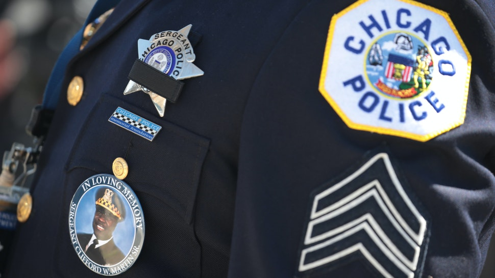 CHICAGO, ILLINOIS - APRIL 21: A police officer wears a button with a picture of Sergeant Clifford Martin, a 25-year veteran of the Chicago Police Department, while attending his funeral on April 21, 2020 in Chicago, Illinois. Martin died on April 10, from complications from COVID-19. In accordance with the social distancing restrictions imposed by the state, only 10 family members were allowed inside the funeral home for the service and police officers joining in the procession were asked to remain in their cars outside of the funeral home during the service. (Photo by Scott Olson/Getty Images)