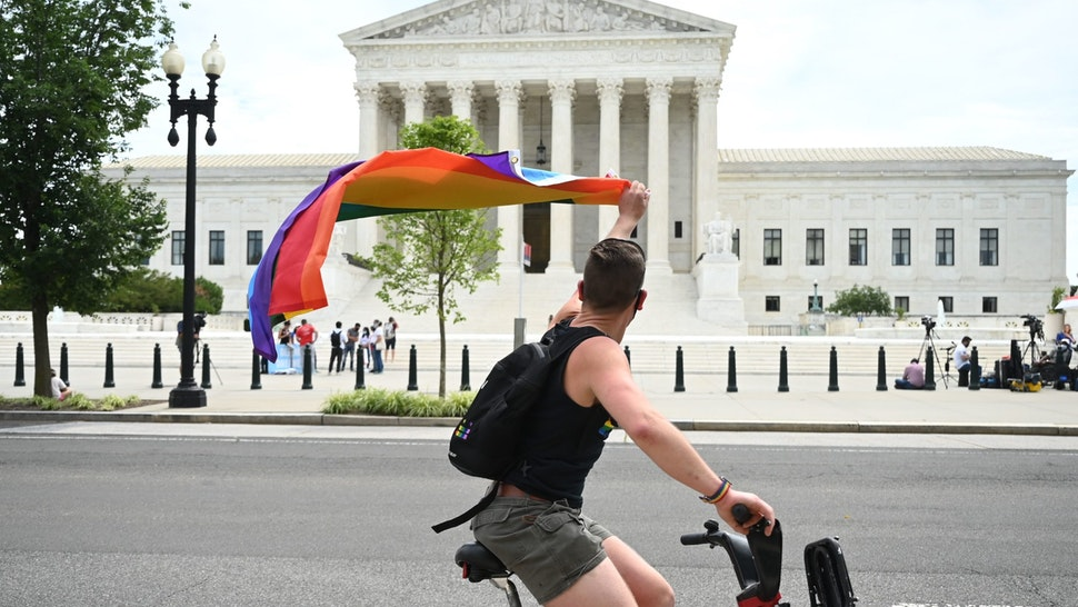 A man waves a rainbow flag as he rides by the US Supreme Court that released a decision that says federal law protects LGBTQ workers from discrimination on June 15, 2020 in Washington,DC. - The US top court has ruled it illegal to fire workers based on sexual orientation. (Photo by JIM WATSON / AFP) (Photo by JIM WATSON/AFP via Getty Images)