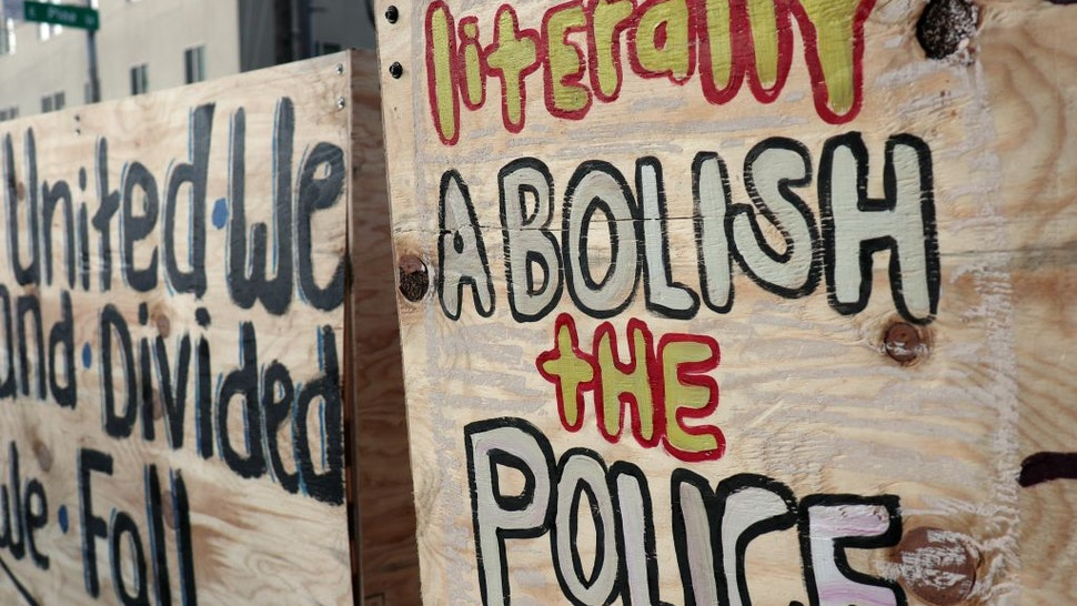 """Graffiti on a barricade inside the so-called """"Capitol Hill Autonomous Zone"""" call for the abolition of police."""