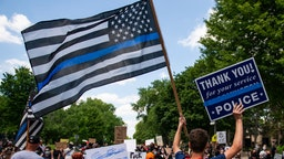 "A demonstrator holds a ""Thin Blue Line"" flag and a sign in support of police during a protest outside the Governors Mansion on June 27, 2020 in St Paul, Minnesota."