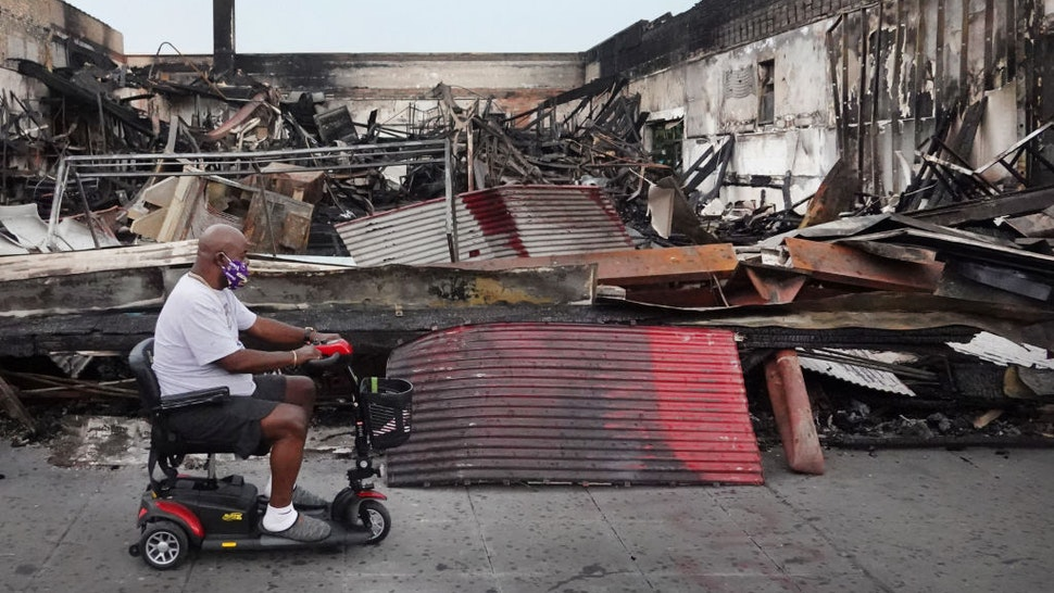 A man rides a scooter past the charred wreckage of a building after being burned to the ground during last week's rioting sparked by the death of George Floyd on June 2, 2020 in Minneapolis, Minnesota.