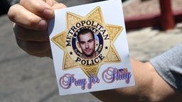 "LAS VEGAS, NEVADA - JUNE 11: A woman displays a sticker she received at an Injured Police Officers Fund (IPOF) of Nevada ""Shay Day"" fundraiser for Las Vegas Metropolitan Police Department Officer Shay Mikalonis at the Sahara West Urgent Care & Wellness parking lot on June 11, 2020 in Las Vegas, Nevada. Mikalonis was shot in the head during an anti-racism protest on the Las Vegas Strip in the wake of George Floyd's death on June 1. He is on a ventilator and is listed in critical condition at University Medical Center of Southern Nevada. Edgar Samaniego, 20, who was not part of the protest, was arrested for the shooting and is facing charges including attempted murder. (Photo by Ethan Miller/Getty Images)"