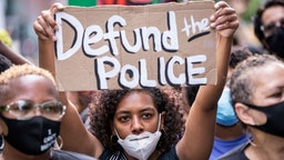 "An African American protester wears a mask and holds a homemade sign that says, ""Defund the Police"" as they perform a peaceful protest walk across the Brooklyn Bridge."