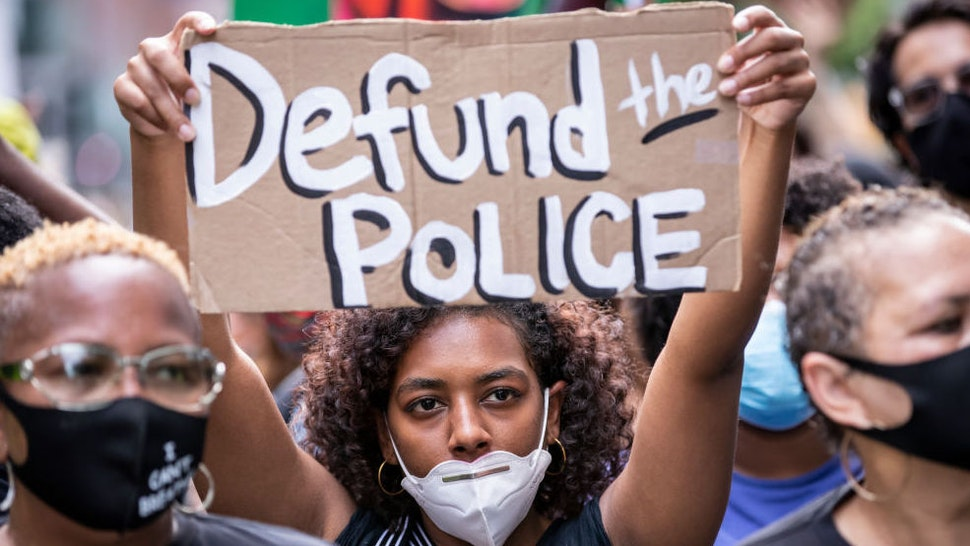 """An African American protester wears a mask and holds a homemade sign that says, """"Defund the Police"""" as they perform a peaceful protest walk across the Brooklyn Bridge."""