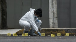 MEXICO CITY, MEXICO - JUNE 26: An expert of the Mexico City government collects bullets from the place where the attack against the Mexico City Police Chief Omar García Harfuch occurred on June 26, 2020 in Mexico City, Mexico. This morning Security Secretary of Mexico City suffered an attack that has been attributed to the Cartel Jalisco Nueva Generacion. Harfuch and his team received medical attention and are reported out of danger but 3 people died in the shootout (2 guards, 1 attacker and a civlian) and 12 were taken under police custody. (Photo by Cristopher Rogel Blanquet/Getty Images)