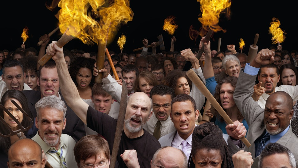 Angry crowd carrying torches - stock photo