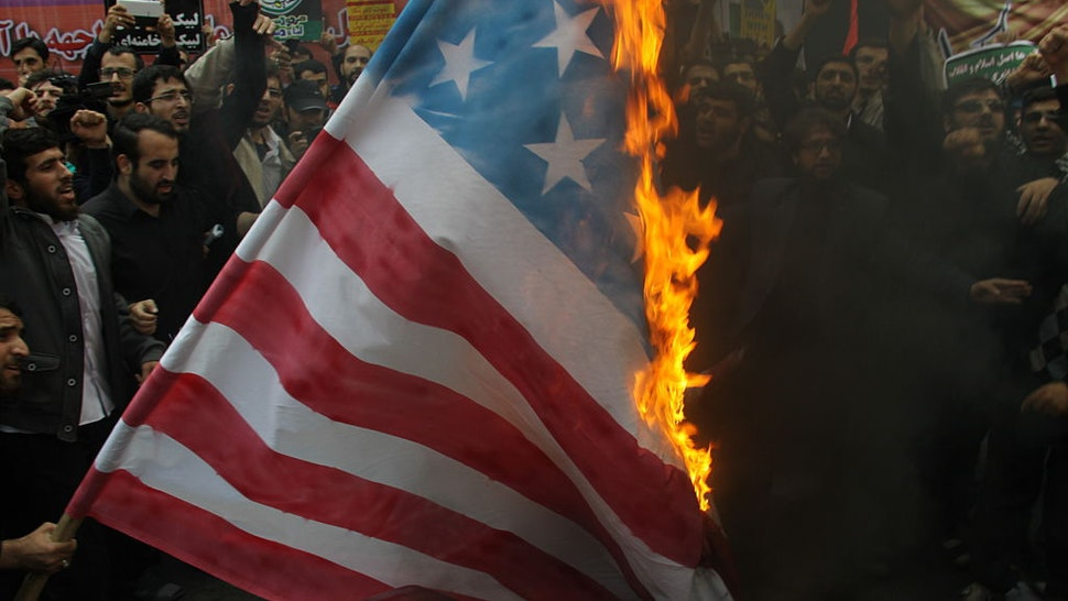 Iranians burn a US flag outside the former US embassy in the Iranian capital Tehran on November 4, 2015, during a demonstration marking the anniversary of its storming by student protesters that triggered a hostage crisis in 1979. Thousands of