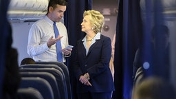 Democratic presidential nominee Hillary Clinton looks at a smart phone with national press secretary Brian Fallon on her plane at Westchester County Airport October 3, 2016 in White Plains, New York.