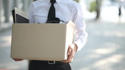 Close-up Of Unemployed Businessperson Carrying Cardboard Box - stock photo