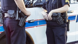 Cropped view of police officers standing beside a squad car having a conversation. The focus is on the policewoman whose hands are resting on her gun belt.
