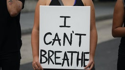 """WASHINGTON, USA - MAY 29: A person holds a banner reading """"I Can't Breathe"""", as crowds gather to protest after the death of George Floyd in Washington D.C. United States on May 29, 2020. Floyd, 46, a black man, was arrested Monday after reportedly attempting to use a counterfeit $20 bill at a local store. Video footage on Facebook showed him handcuffed and cooperating. But police claimed he resisted arrest. A white officer kneeled on his neck, despite Floyd√¢s repeated pleas of """"I can't breathe."""" Former police officer Derek Chauvin was charged with third-degree murder and manslaughter, according to Hennepin County Prosecutor Michael Freeman. Minneapolis, Minnesota Mayor Jacob Frey said Friday he imposed a mandatory curfew because of ongoing protests regarding the death of George Floyd."""
