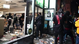 """People loot a store during demonstrations over the death of George Floyd by a Minneapolis police officer on June 1, 2020 in New York. - New York's mayor Bill de Blasio today declared a city curfew from 11:00 pm to 5:00 am, as sometimes violent anti-racism protests roil communities nationwide. Saying that """"we support peaceful protest,"""" De Blasio tweeted he had made the decision in consultation with the state's governor Andrew Cuomo, following the lead of many large US cities that instituted curfews in a bid to clamp down on violence and looting."""