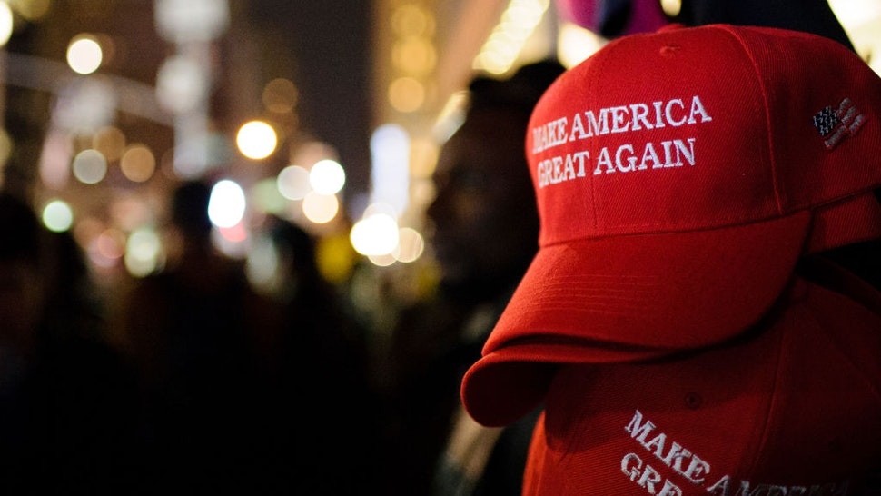 """MANHATTAN, NEW YORK CITY, NEW YORK, UNITED STATES - 2016/11/09: """"Make America Great Again"""" red baseball caps, signature headwear of the Donald Trump campaign and its supporters, stand on sale on 6th Avenue in Midtown Manhattan in the second hour after Election Day as election results point to a shock Trump win."""