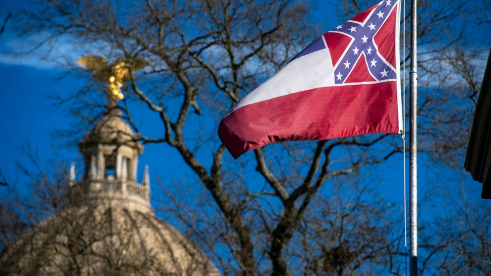 Jackson, MS - JANUARY 10: The Mississippi State Capitol dome is visible in the distance as the flag of the state of Mississippi flies nearby in Jackson, MS on January 10, 2019.