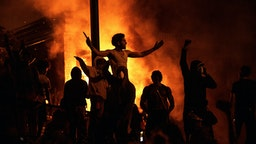 MINNEAPOLIS, MN - MAY 28: Protesters cheer as the Third Police Precinct burns behind them on May 28, 2020 in Minneapolis, Minnesota. As unrest continues after the death of George Floyd police abandoned the precinct building, allowing protesters to set fire to it.