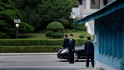 Members of North Korean security stands guard near a North Korean motorcade while US President Donald Trump and North Korea's leader Kim Jong-un meet in the Demilitarized Zone(DMZ) on June 30, 2019.