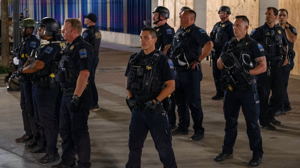Tulsa Police Department officers stand in formation after leaving the area after shooting pepper balls at protesters as they marched and protested near the BOK Center in Tulsa, Oklahoma on June 20,2020 - Hundreds of supporters lined up early for Donald Trump's first political rally in months, saying the risk of contracting COVID-19 in a big, packed arena would not keep them from hearing the president's campaign message.