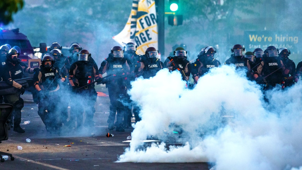 """Smoke rises near a row of police in riot gear near the 5th police precinct during a demonstration to call for justice for George Floyd, a black man who died while in custody of the Minneapolis police, on May 30, 2020 in Minneapolis, Minnesota. - Clashes broke out and major cities imposed curfews as America began another night of unrest Saturday with angry demonstrators ignoring warnings from President Donald Trump that his government would stop violent protests over police brutality """"cold."""""""