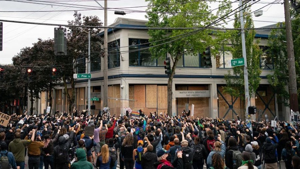 Demonstrators hold a rally and teach-in outside of the Seattle Police Department's East Precinct, which has been boarded up and protected by fencing, on June 8, 2020 in Seattle, Washington. Seattle Police and Washington National Guard personnel vacated the area after the previous night saw violent clashes in the vicinity during ongoing Black Lives Matter protests in the wake of George Floyds death. (Photo by David Ryder/Getty Images)