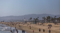 People enjoy Venice Beach during the first day of the Memorial Day holiday weekend during the novel Coronavirus, COVID-19, pandemic in California on May 23, 2020. - Los Angeles County officials announced May 22, 2020, that beach bike paths and some beach parking lots will reopen and curbside service at indoor malls will be permitted. The county reopened its beaches a week ago but kept beach parking lots, bike paths, piers and boardwalks closed. (Photo by Apu GOMES / AFP)