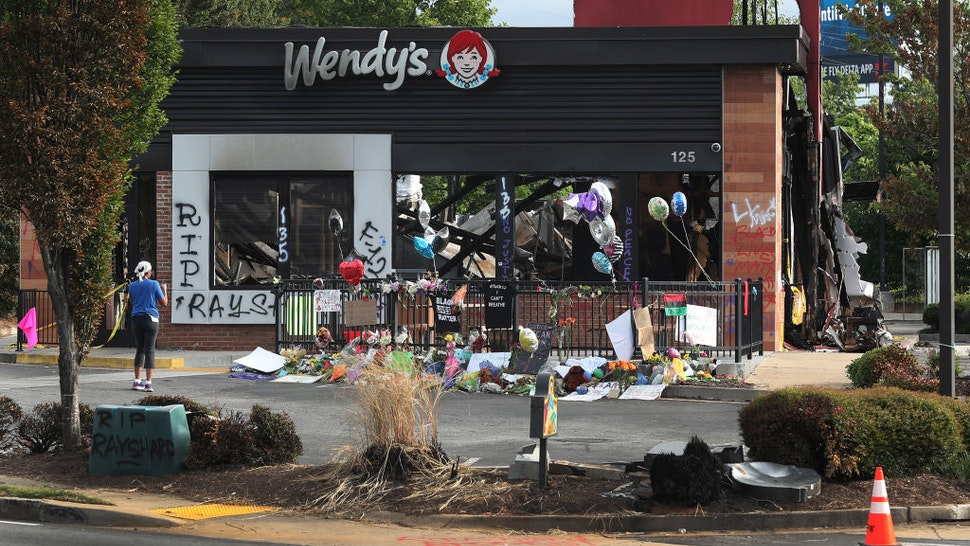 ATLANTA, GEORGIA - JUNE 17: People visit the memorial setup outside the Wendy's restaurant that was set on fire by demonstrators after Rayshard Brooks was killed on June 17, 2020 in Atlanta, Georgia. The site has become a place of remembrance for Mr. Brooks, who was killed by police while fleeing after a struggle during a field sobriety test in the Wendy's parking lot. (Photo by Joe Raedle/Getty Images)