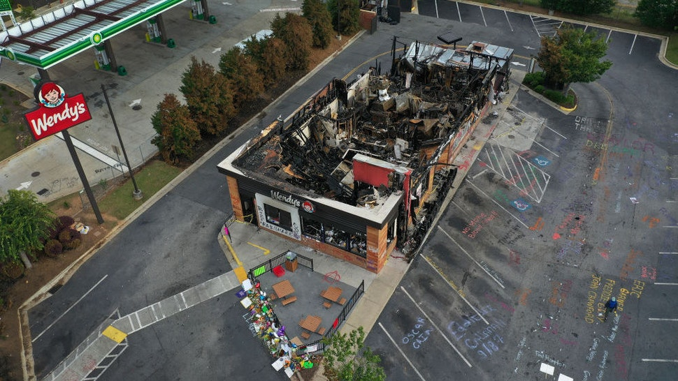 In this aerial photo, the Wendy's restaurant that was set on fire by demonstrators after Rayshard Brooks was killed is seen on June 17, 2020 in Atlanta, Georgia. The site has become a place of remembrance for Mr. Brooks, who was killed by police while fleeing after a struggle during a field sobriety test in the Wendy's parking lot. (Photo by Joe Raedle/Getty Images)