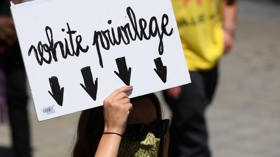 """A woman holds a placard reading """"White privilege"""" during a demonstration on June 14, 2020, in Barcelona, as part of the worldwide protests against racism and police brutality. - The protests are part of a worldwide movement following the killing in the United States of African-American man George Floyd who died after a white policeman knelt on his neck for several minutes. (Photo by Josep LAGO / AFP)"""