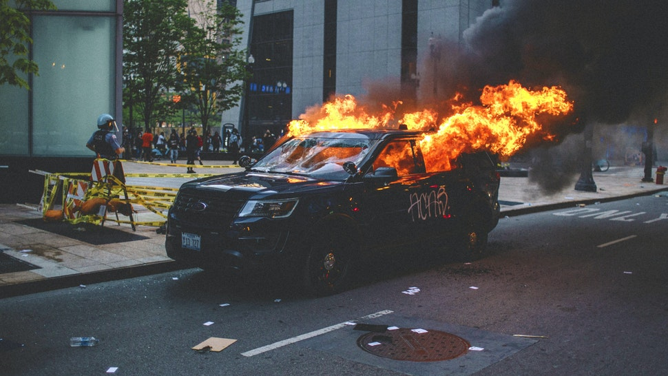 Protesters set fire to a police vehicle , on May 30, 2020 during a protest against the death of George Floyd, an unarmed black man who died while while being arrested and pinned to the ground by the knee of a Minneapolis police officer.