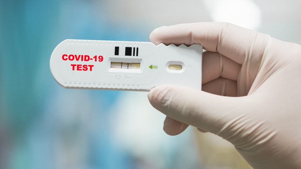 Doctor hand holding positive Coronavirus or Covid-19 rapid test