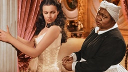 Vivien Leigh (1913-1967), British actress, has her corset tightened by Hattie McDaniel (1892–1952), US actress, in a publicity still issued for the film, 'Gone with the Wind', 1939. The drama, directed by Victor Fleming (1889-1949), starred Leigh as 'Scarlett O'Hara', and McDaniel as 'Mammy'. (Photo by