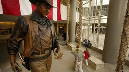 (Santa Ana) Passengers file by the statue of John Wayne at John Wayne Airport. There s a proposal floating around to change the name of John Wayne Airport to the O.C. What do people have to say? Photo taken Tuesday June 8, 2004. (Photo by