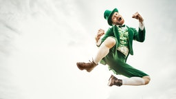 A stereotypical Irish character all ready for Saint Patricks day jumps and dances in an open field of Irish country side. Copy space in the sky and grass.