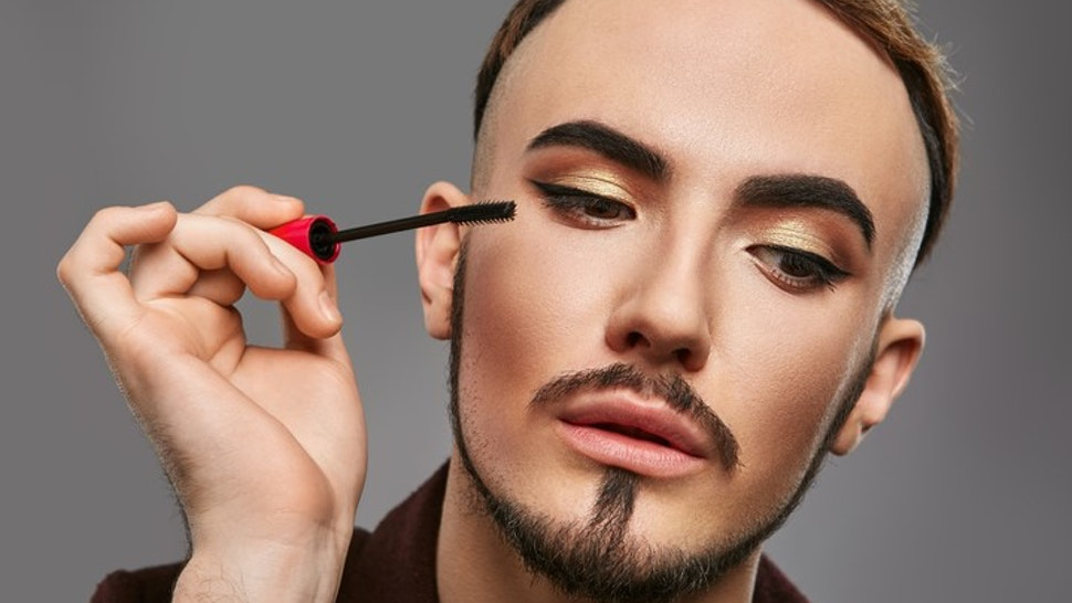 Man Applying Eyeliner Against Gray Background