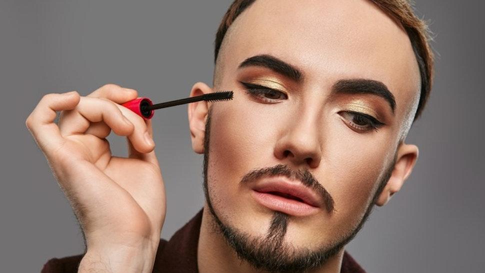 Man Applying Eyeliner Against Gray Background