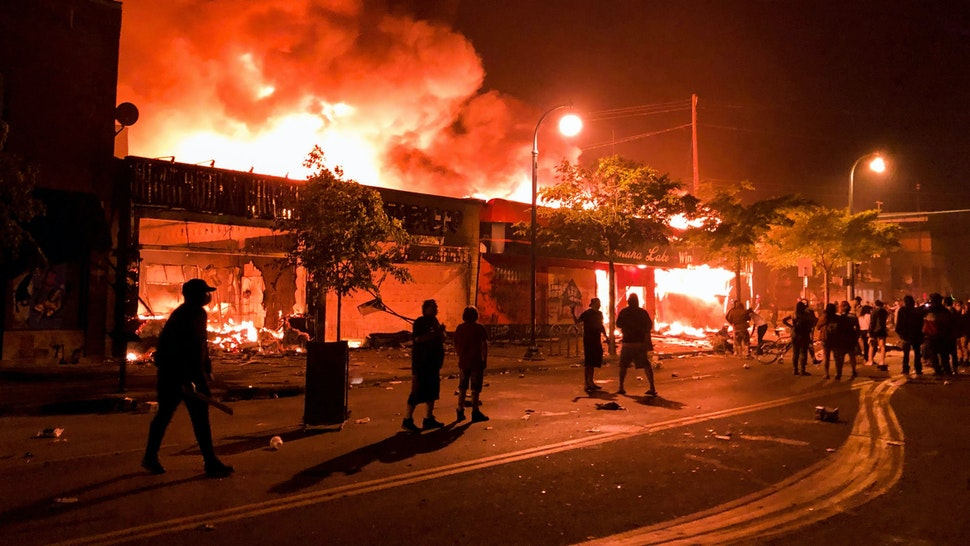 TOPSHOT - Flames rise from a liquor store and shops near the Third Police Precinct on May 28, 2020 in Minneapolis, Minnesota, during a protest over the death of George Floyd, an unarmed black man, who died after a police officer kneeled on his neck for several minutes. - A police precinct in Minnesota went up in flames late on May 28 in a third day of demonstrations as the so-called Twin Cities of Minneapolis and St. Paul seethed over the shocking police killing of a handcuffed black man. The precinct, which police had abandoned, burned after a group of protesters pushed through barriers around the building, breaking windows and chanting slogans. A much larger crowd demonstrated as the building went up in flames.