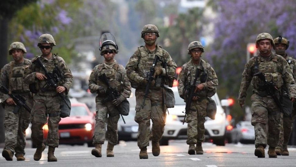 Armed National Guard soldiers patrol on Hollywood Blvd, June 1, 2020 in Hollywood, California as peaceful protests and looting continue in Los Angeles County. - Major US cities -- convulsed by protests, clashes with police and looting since the death in Minneapolis police custody of George Floyd a week ago -- braced Monday for another night of unrest. More than 40 cities have imposed curfews after consecutive nights of tension that included looting and the trashing of parked cars. (Photo by Robyn Beck / AFP) (Photo by