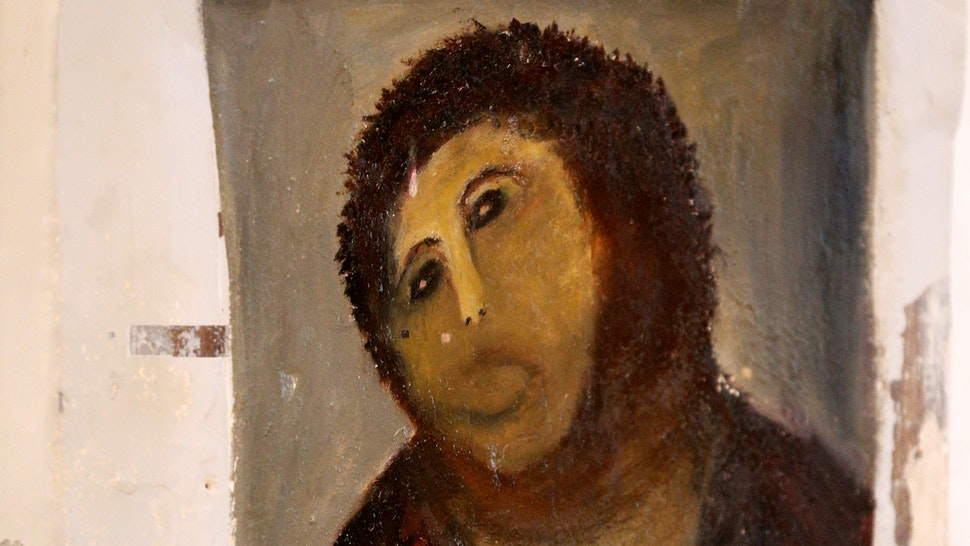 """View of the deteriorated version of """"Ecce Homo"""" by 19th-century painter Elias Garcia Martinez, at the Borja Church in Zaragoza on August 28, 2012. An elderly woman's catastrophic attempt to """"restore"""" a century-old oil painting of Christ in a Spanish church has provoked popular uproar, and amusement. Titled """"Ecce Homo"""" (Behold the Man), the original was no masterpiece, painted in two hours in 1910 by a certain Elias Garcia Martinez directly on a column in the church at Borja, northeastern Spain. The well-intentioned but ham-fisted amateur artist, in her 80s, took it upon herself to fill in the patches and paint over the original work, which depicted Christ crowned with thorns, his sorrowful gaze lifted to heaven. AFP PHOTO / CESAR MANSO (Photo credit should read"""