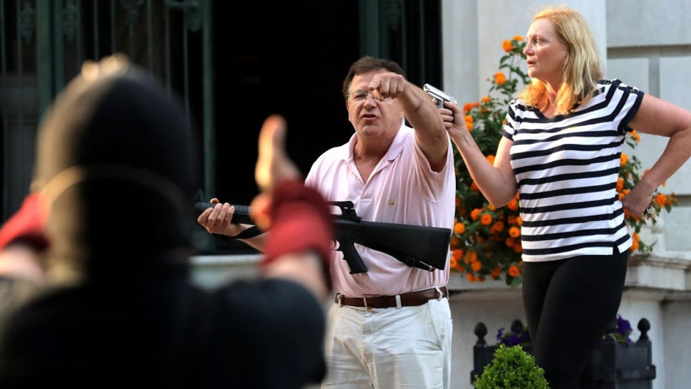 Armed homeowners standing in front of their house along Portland Place confront protesters as they march to Mayor Lyda Krewson's house on Sunday, June 28, 2020, in the Central West End in St. Louis. (