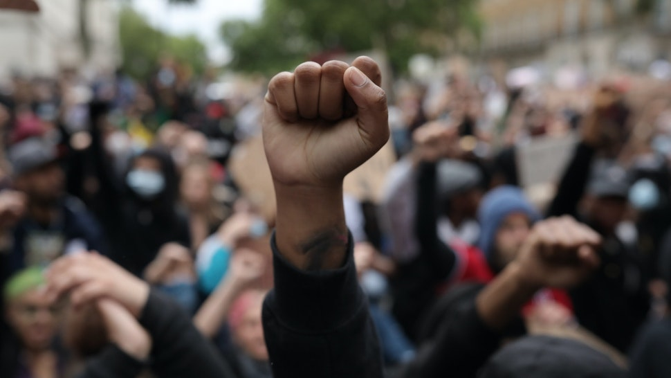 Protesters raise clenched fists during a Black Lives Matter protest outside the Houses of Parliament on June 3, 2020 in London, United Kingdom.